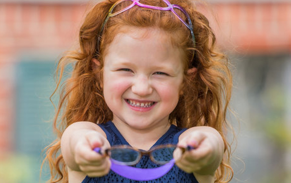 Little girl with red hair holding up glasses