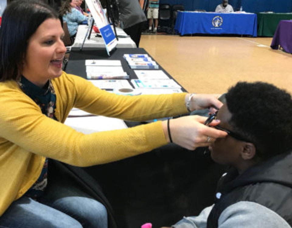 A woman helping adjust a boy's glasses